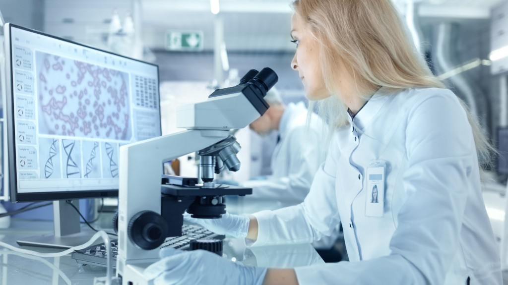 Female Research Scientist Using Electronic Microscope. She and H